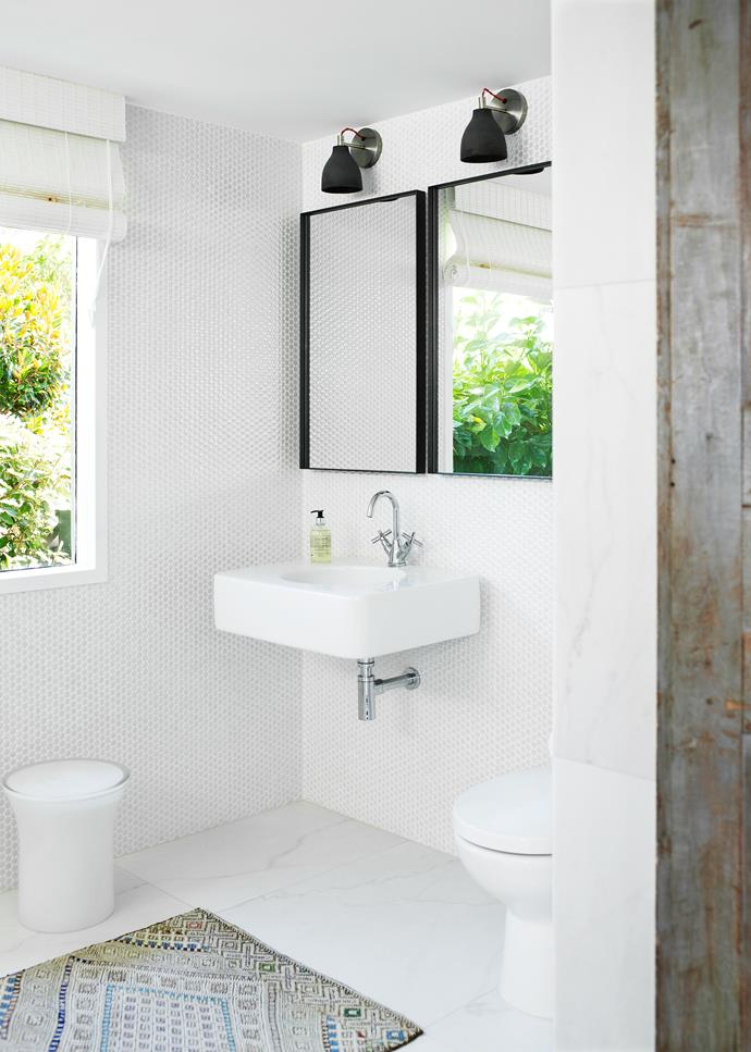 "Glossy tiles bounce sunlight around a pared-back bathroom. ""It's designed as a wet room and it's really spacious. The window is covered by foliage, which adds a fresh touch and makes it more soft and interesting,"" says interior designer [Justine Hugh-Jones Design](http://www.justinehughjones.com/