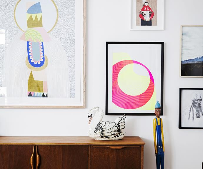 Artwork covered wall with credenza