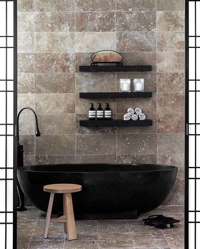 "This dark-toned bathroom gives a nod to Japanese bathing traditions in granite and travertine. ""The bath is positioned as the central focus of the room and the intentional use of black was to create an interesting silhouette effect,"" says designer Andrea D'Cruz.   Seascapes stone bath and base in Nero from [Apaiser](http://www.apaiser.com/