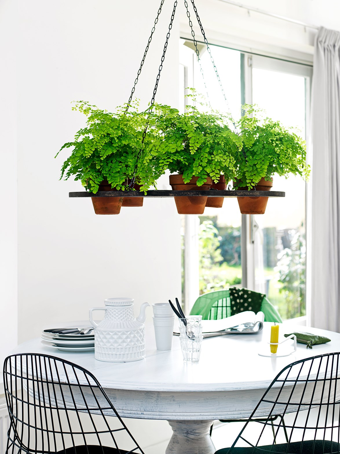 A hanging plant display brings life to this small dining space.
