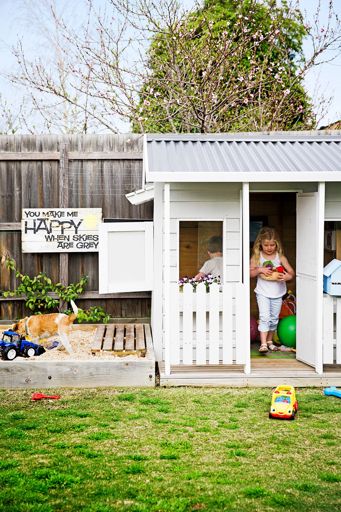 Young Georgina and Thomas love to play in their white weatherboard cubbyhouse and Biscuit the dog is in heaven in the sandpit.