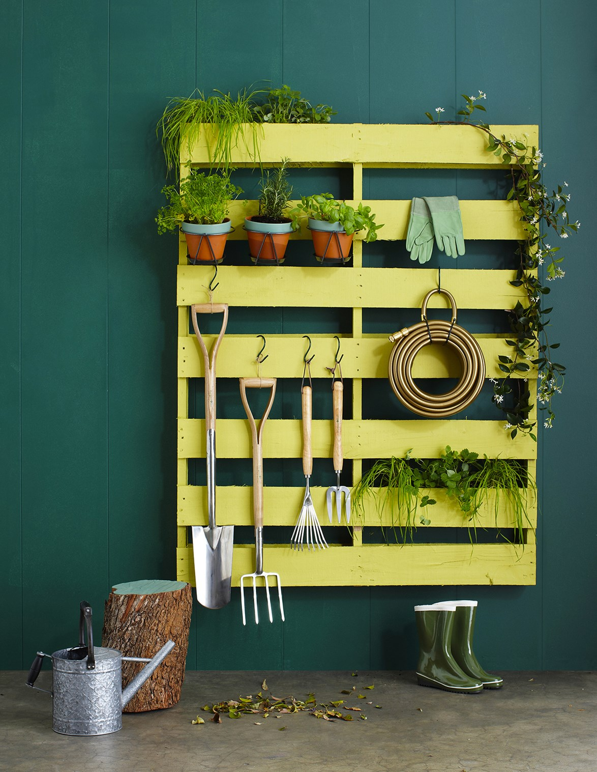 Recycle and paint an old pallet to jazz up an outdoor space. A vibrantly painted pallet is the ideal place to store garden tools and hang herbs for easy access.