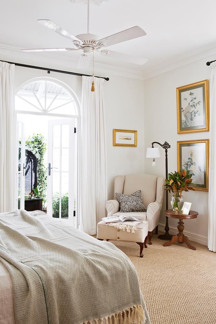 """French doors with an arched fanlight set a romantic tone in the master bedroom.   **Bedlinen** from [Sheridan](http://www.sheridan.com.au/ target=""""_blank""""). Custom-made **curtains and rods** from [Spotlight](https://www.spotlight.com.au/ target=""""_blank""""). **Side table** from [East West Design](http://www.eastwestdesign.com.au/ target=""""_blank""""). **Fan** from [Tilly's Lights](http://www.tillyslights.com.au/ target=""""_blank""""). **Carpet** from [Floors Natural](http://www.floorsnatural.com.au/ target=""""_blank"""")."""