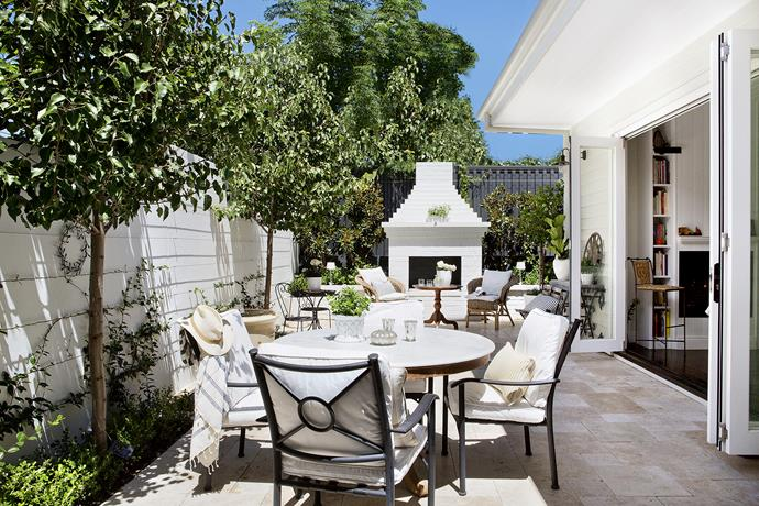 """Every detail counts in this well-resolved outdoor space. Even the fireplace has an elegant stepped pediment. The potted lemon is underplanted with white vincas and thyme.   **Chairs** from [Harvey Norman](http://www.harveynorman.com.au/ target=""""_blank""""). French travertine **paving** from [Bernini Stone & Tiles](http://www.bernini.com.au/ target=""""_blank""""). **Towel** from [Ottoman Hamam](http://www.ottomanhamam.com.au/ target=""""_blank""""). Small **cushions** from [Busatti](http://www.busatti.com.au/ target=""""_blank"""")."""