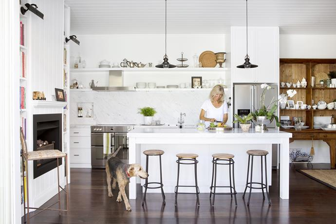 """Homeowner Beverley, pictured with Ruby the Airedale terrier, designed the new kitchen layout herself.   **Benchtop** and **splashback** in honed Santorini marble from [Bernini Stone & Tiles](http://www.bernini.com.au/ target=""""_blank""""). **Stools** from [Corner Store](https://www.cornerstore.net.au/ target=""""_blank"""") (tall) and [Ikea](http://www.ikea.com.au/ target=""""_blank""""). **Pendant lights** from Subiaco Restoration. **Cooktop** and **fridge** from [Harvey Norman](http://www.harveynorman.com.au/ target=""""_blank""""). **Tapware** and **sink** from [Sink Warehouse](http://www.sinkwarehouse.com.au/ target=""""_blank"""")."""