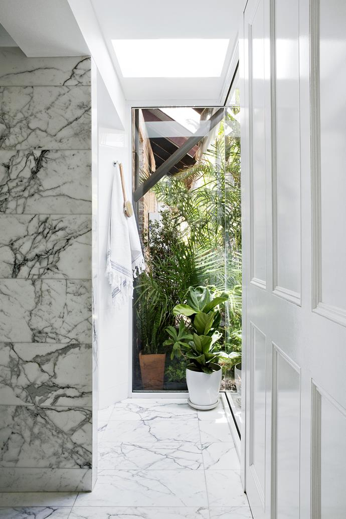 """Glazed walls with green views and a skylight give the master ensuite an indoor-outdoor feel.   Santorini **marble** from [Bernini Stone & Tiles](http://www.bernini.com.au/ target=""""_blank""""). **Tiling** by The Tilist. **Skylight** by [Velux](http://www.velux.com.au/ target=""""_blank""""). **Towel** from [Ottoman Hamam](http://www.ottomanhamam.com.au/ target=""""_blank""""). Potted **fiddle leaf fig** from [Waldecks](http://www.waldecks.com.au/ target=""""_blank"""")."""