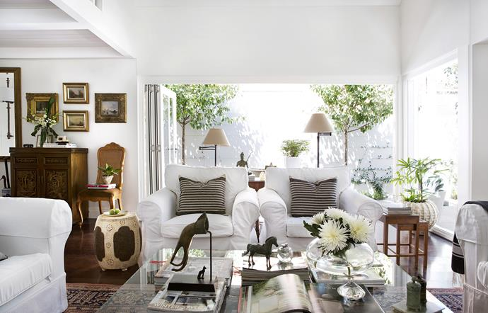 """There's a strong sense of symmetry in Beverley's decorating. Outside, a pair of Manchurian pear trees frame the courtyard view.   Twin **floor lamps** from [Lightingales](http://www.lightingales.com.au/ target=""""_blank""""). Striped linen **cushions** from [Busatti](http://www.busatti.com.au/ target=""""_blank"""")."""