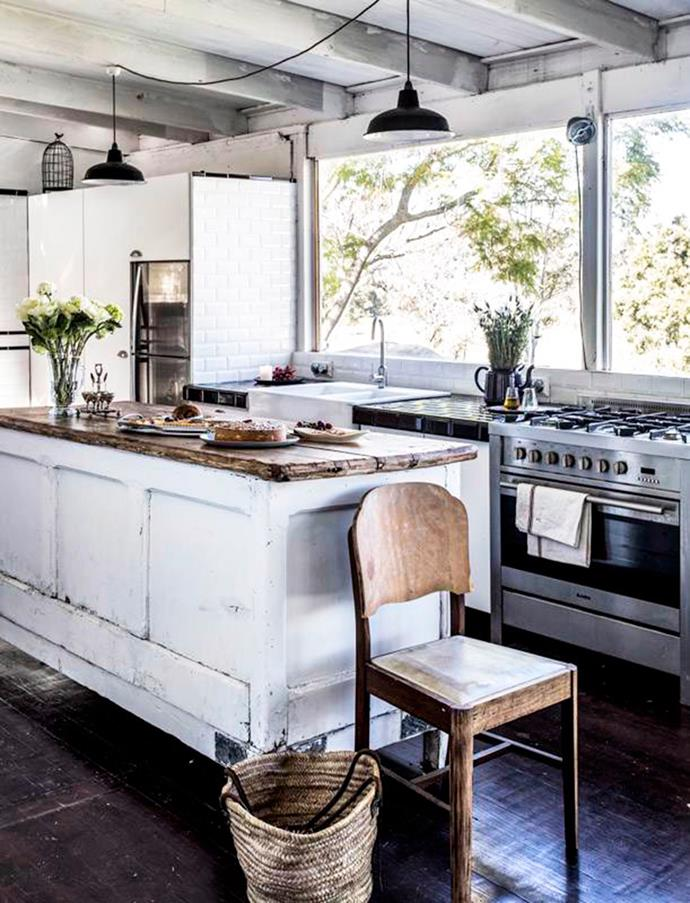 A worn-timber island and vases of fresh flowers adds to the rustic country feel of this kitchen. Photo: Felix Forest / bauersyndication.com.au.