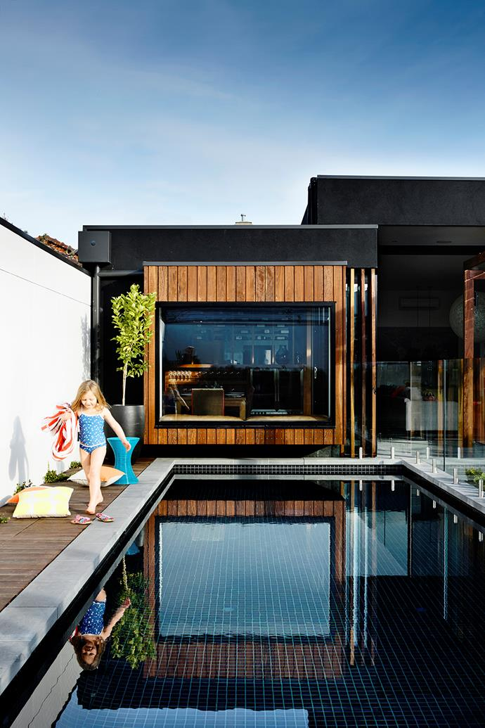 "This 9x3m pool in Melbourne was designed to be ""season-less"", says owner Andy Mullins. ""We wanted it to be an exciting space to dine by, swim in, walk past and look at from inside with the fire going."" A dark-tiled interior is combined with bullnose bluestone tiles and spotted gum decking.   **Cost:** about $85,000.   Photo: Derek Swalwell"