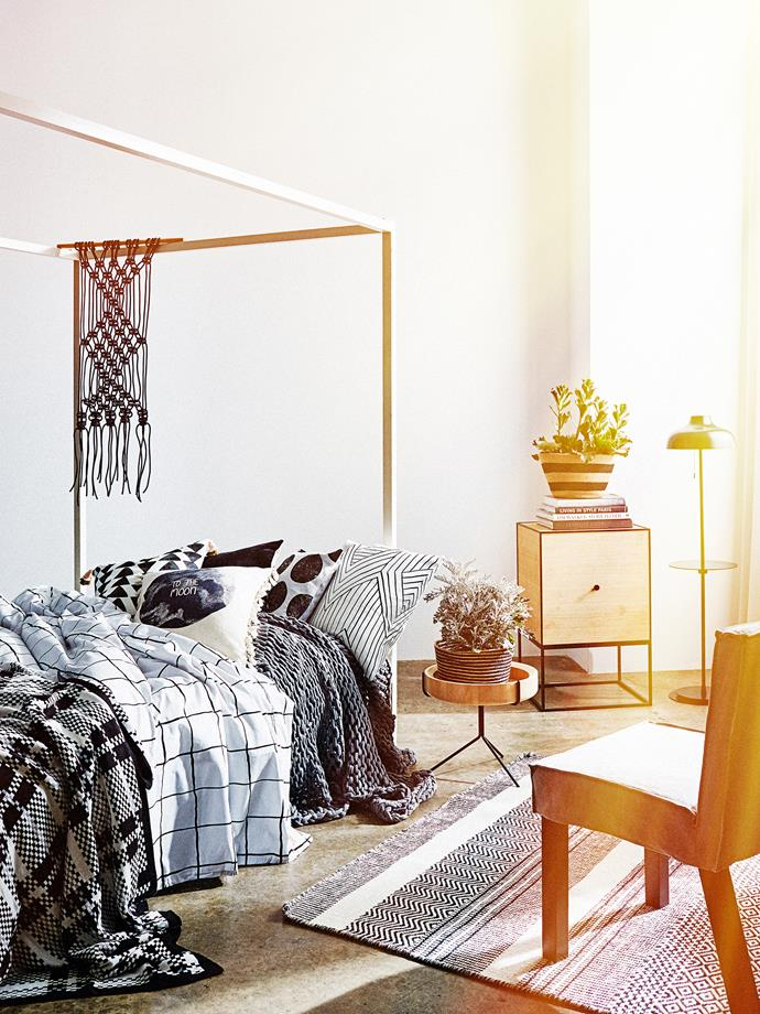 **Pattern clash:**  Grids, circles and triangles lend a geometric element to this monochrome bedroom. Woven accessories with a tribal vibe warm up the look. Photo: Brett Stevens / *real living*