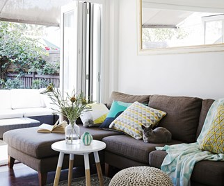 Brown corner sofa with coloured cushions