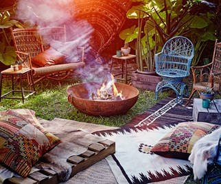 Fire pit in garden surrounded by cushions