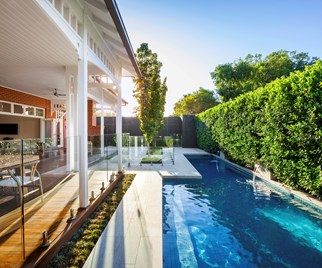 Lap pool in backyard with water feature