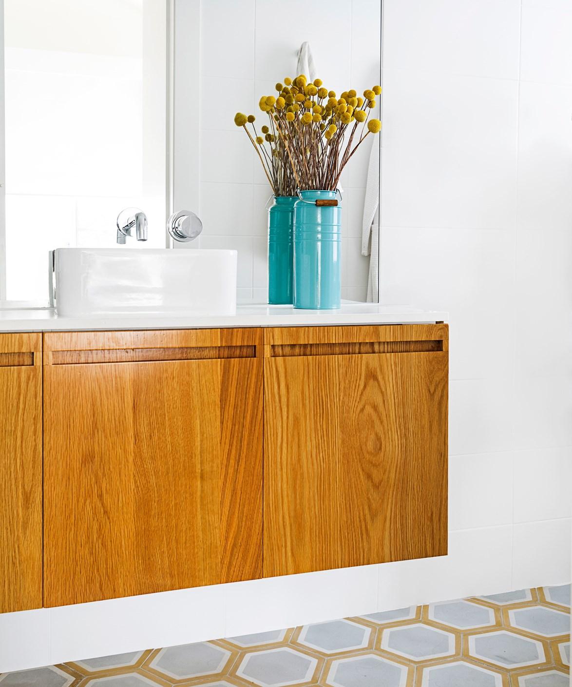 "Hexagonal floor tiles echo the warm honey shades of the timber vanity. This [home on Bondi beach](https://www.homestolove.com.au/gallery-romy-alwills-budget-conscious-renovation-1963|target=""_blank"") belongs to interior designer Romy Alwill."
