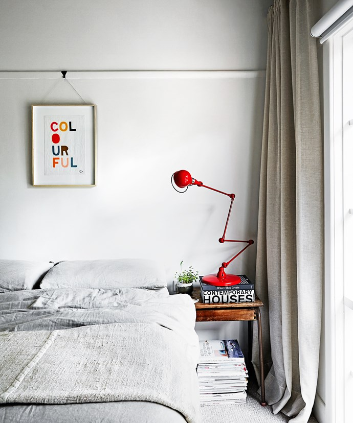 """In the main bedroom, art adds a pop of colour, along with the original Jielde lamp. An old flip-lid school desk is used as a bedside table. The lamp, a classic mid-century French design, was for a client, but two were accidentally sent so the family got to keep this one.  Jielde **lamp** from [Euroluce](http://euroluce.com.au/