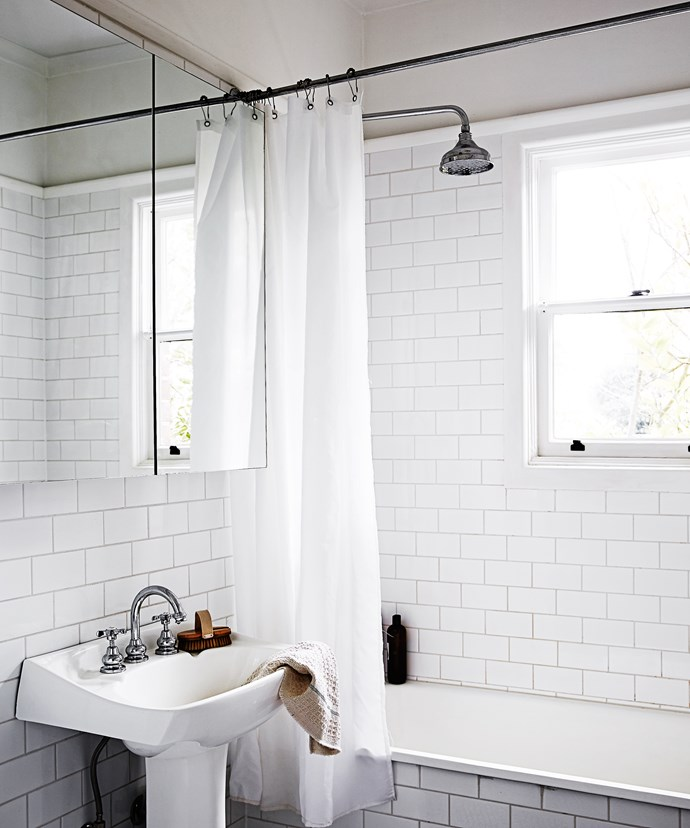 Tiles and tapware in the bathroom were chosen with the home's 1950s mid-century era in mind. The salvaged basin pedestal was refinished in white.
