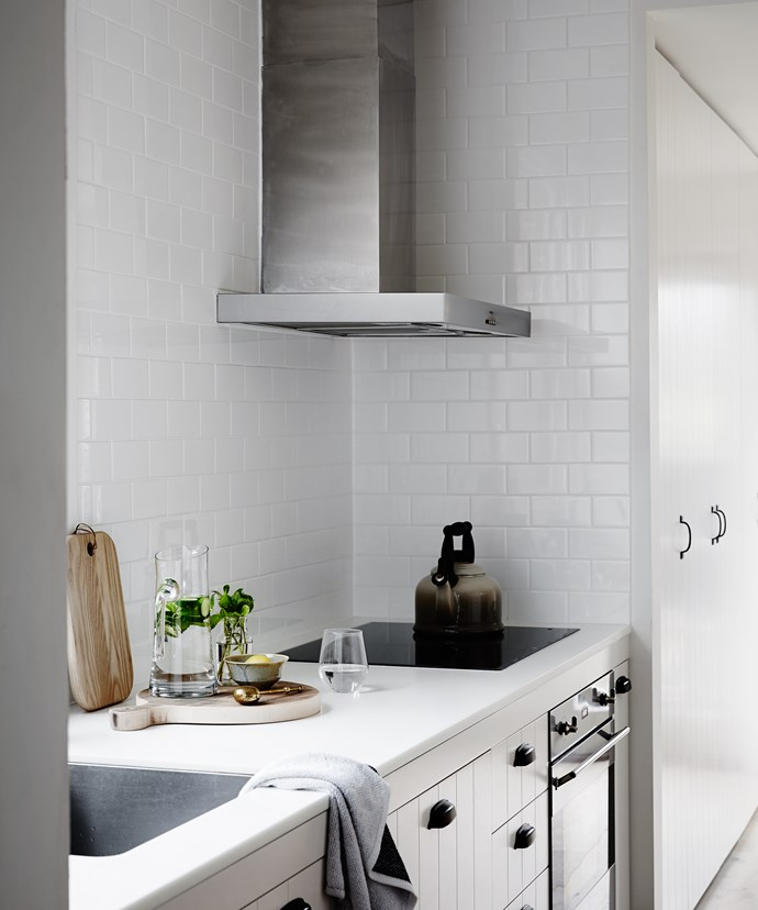 The small kitchen was gutted and redone with little decoration save for a select few pieces in natural materials, keeping it clean and simple – a typical Scandi-style modernist touch. White cabinetry and classic subway tiles are complemented with black handles.