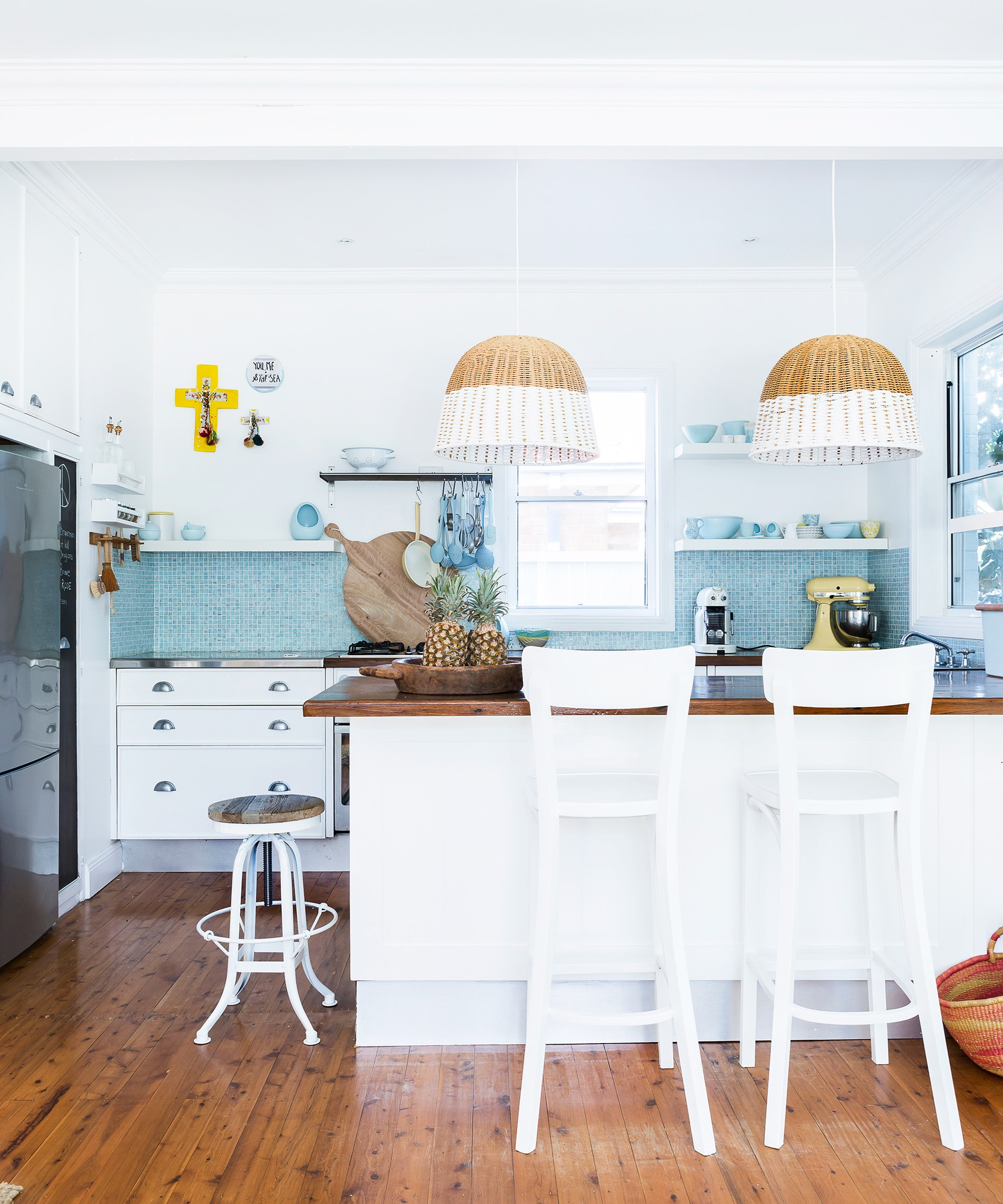 """Accessories on open shelves echo the blue splashback tiles in the kitchen of this breezy beach house. Homeowner Bernadette based her tile choice on the feature colour she has paired with white throughout the home: [Dulux](http://www.dulux.com.au/?utm_campaign=supplier/