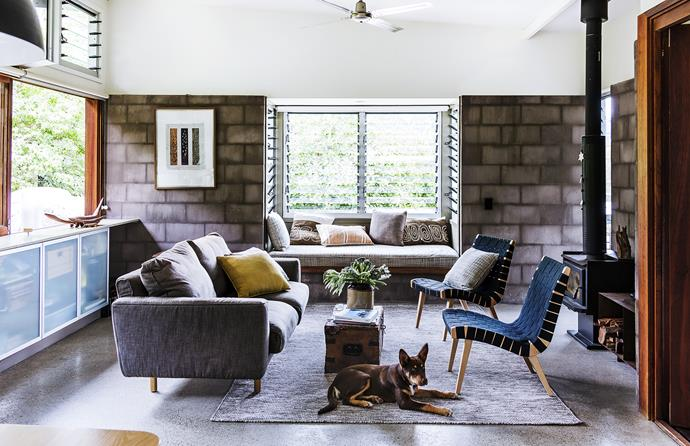 """I love sitting in the bay window in the living room looking up to the cliffs, especially when the gully is running and the frogs are going off,"" says Chris. The polished-concrete slab and reverse concrete-block veneer help promote thermal mass while serving as design elements.   Knoll Risom **chairs** from [Dedece](http://www.dedece.com.au/