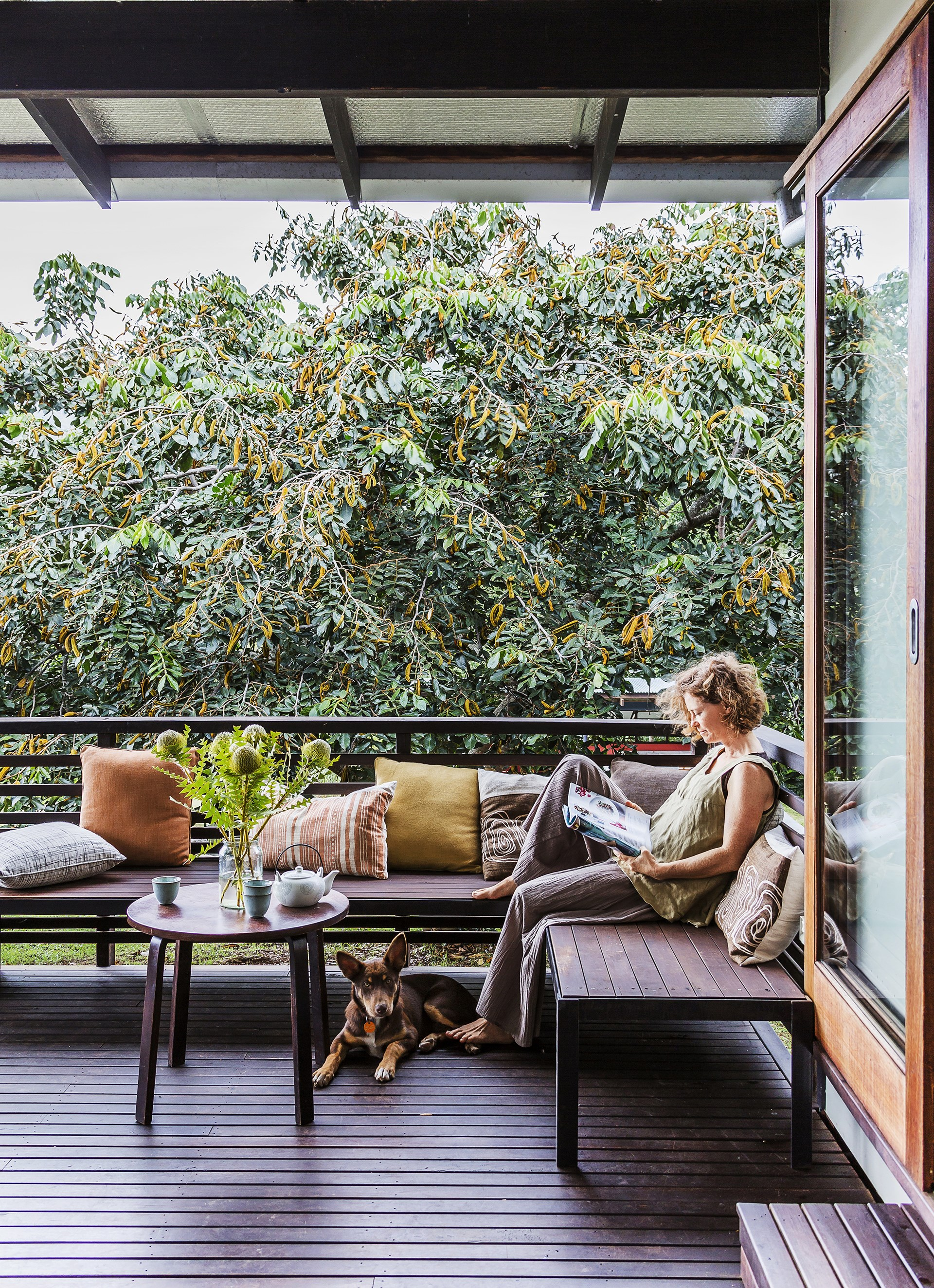 "With a glorious ice-cream bean tree as backdrop, the owner relaxes on the front deck of her [eco-friendly home](http://www.homestolove.com.au/gallery-chris-and-sonias-eco-friendly-queensland-bush-home-1990|target=""_blank"") in the lush hinterland behind Brisbane. *Photo:* Maree Homer"