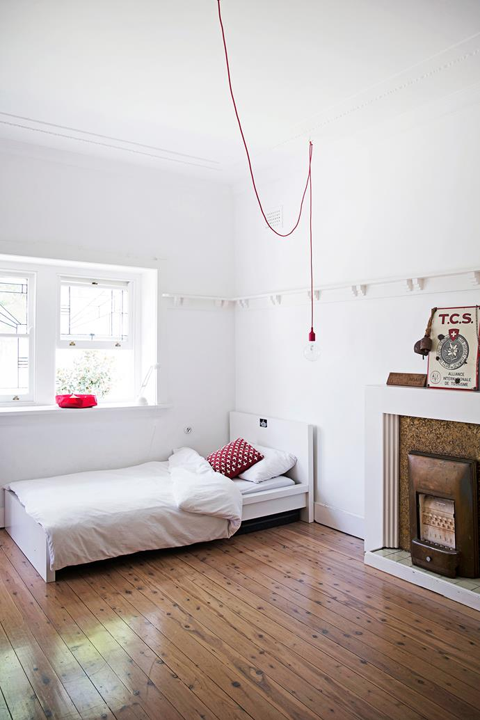 Downstairs, in the older part of the home, is son Noah's bedroom, previously the main bedroom. Pops of red inject colour into an otherwise neutral room. Hooking the electrical cable of a light from a central point in the room adds interest.