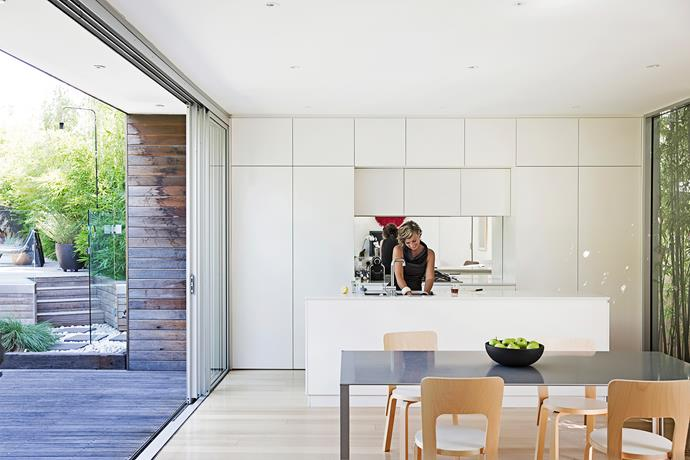 Homeowner Ariana in her new kitchen. The space was completely reworked to reconsider the easterly aspect of the house. White units and a mirrored splashback were added to help bounce light into the space.