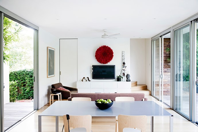 """The new living area, facing the kitchen inside the new extension. Accents of red have been used throughout the home by designer Eva-Marie. A red feather Juju hat from [Safari Fusion](http://www.safarifusion.com.au/