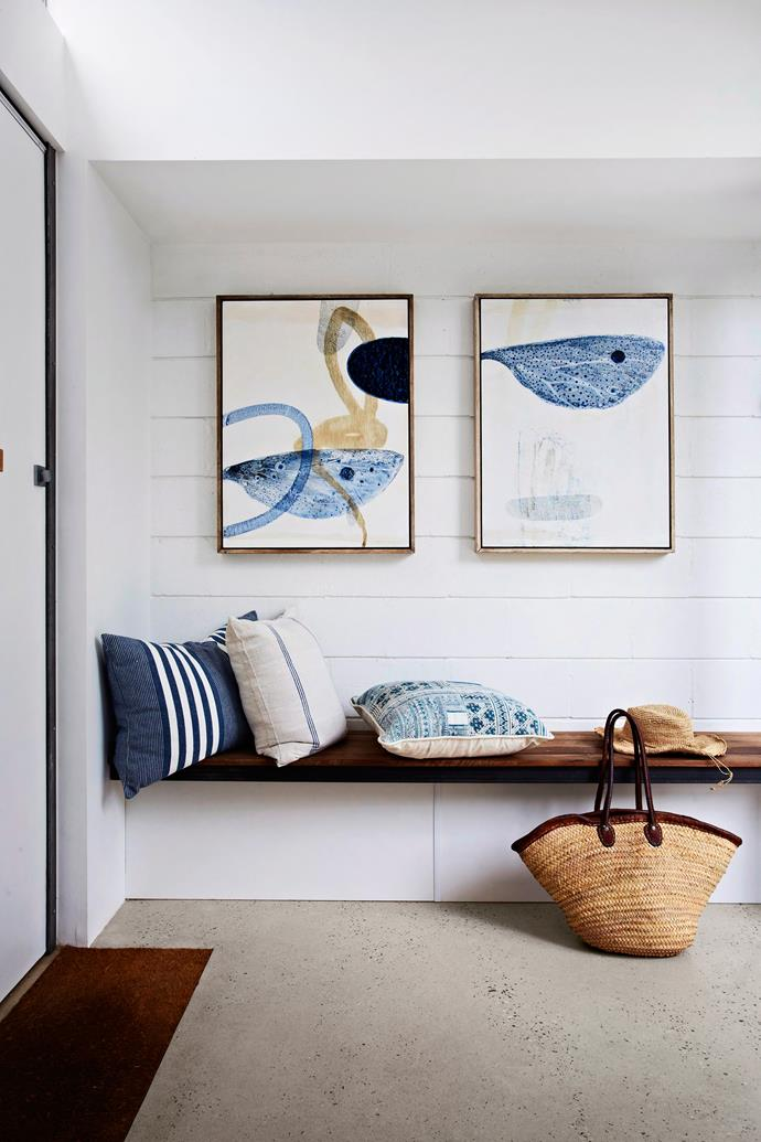 A bench seat in the entry of this renovated Art Deco Melbourne home offers a place to pause and enjoy the surroundings. Blue and white adds a serene nautical touch. Artworks by Graeme Altmann. Photo: Armelle Habib / bauersyndication.com.au