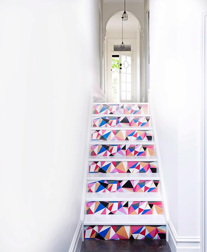 Once visitors would be faced with dark walls and floors. Now stair rises finished in geometric wallpaper make this front hallway a space you won't forget. Photo: Maree Homer / bauersyndication.com.au