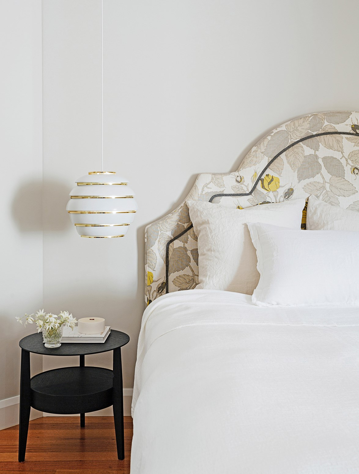 "Crisp white sheets, fluffy pillows and a beautiful upholstered bedhead create a soft and dreamy place to rest in the bedroom of this [feminine Sydney home](https://www.homestolove.com.au/gallery-master-stroke-feminine-sydney-house-design-1-2021|target=""_blank""). The brass pendant adds a welcomed touch of bling. Photo: Felix Forest / *real living*"