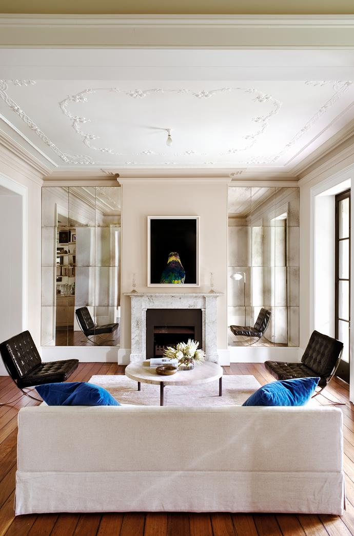 """I love the tension created by playing with contrasting elements; a tension of aesthetic contradiction."" says Siobhan. Walls of aged mirror bounce light around the formal sitting area, while Mies van der Rohe Barcelona chairs and a travertine coffee table from [Spence & Lyda](http://www.spenceandlyda.com.au/