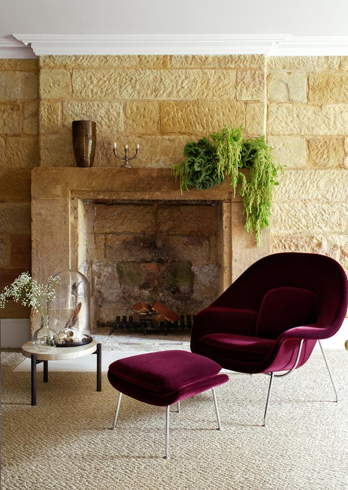 "An Eero Saarinen plum velvet Womb chair and ottoman from [Dedece](http://www.dedece.com/|target=""_blank"") and Ten10 travertine side table in the sandstone-clad study."