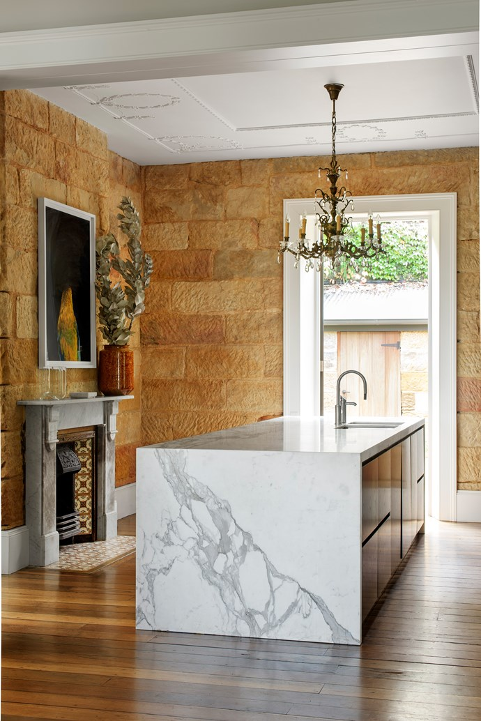 The kitchen is spare and monochrome to contrast with the warmth and texture of the abundant sandstone, with ebony-stained timber veneer and white marble. An antique chandelier hangs above the island.