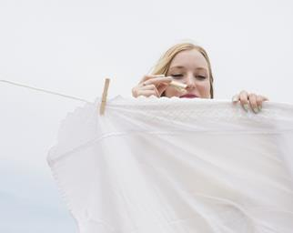 Woman hanging a white sheet on a clothesline