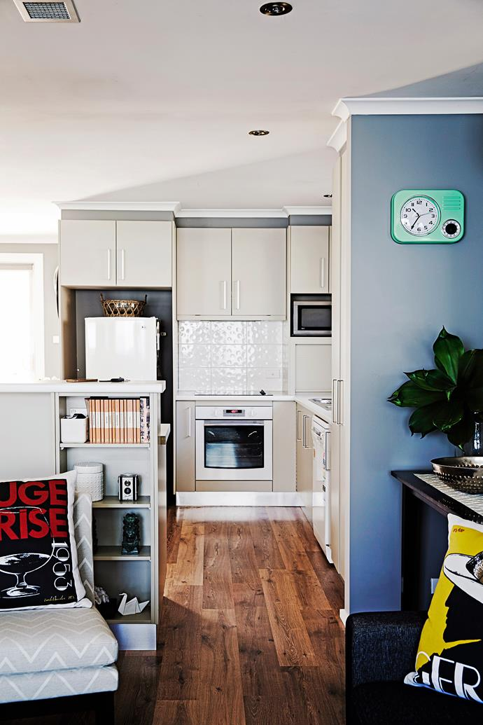Pre-existing shelves on the kitchen island are used to display a quirky collection of objects, books and knick-knacks.