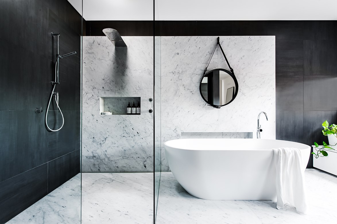 """Marble is complemented by charcoal porcelain tiles and a custom-made vanity in this sharp and edgy [monochrome bathroom](https://www.homestolove.com.au/bathroom-profile-rock-steady-2038