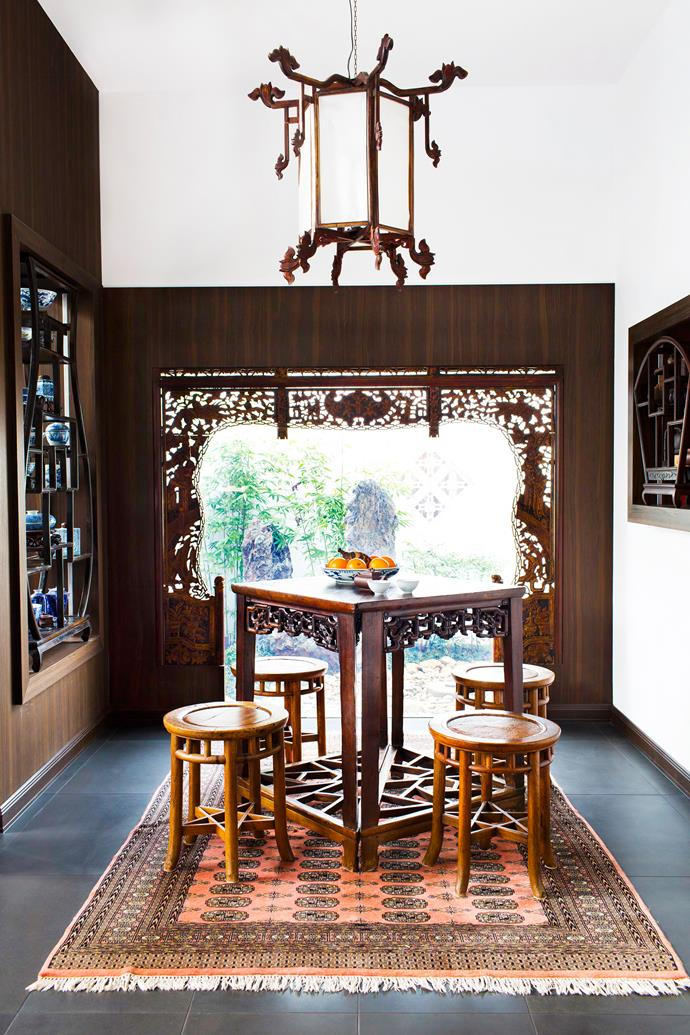 In the tea room that adjoins the dining room, an ornate antique bed canopy has been repurposed as a decorative window frame.   Antique **tea table** and **stools** bought in Hong Kong. **Rug** from Pakistan.