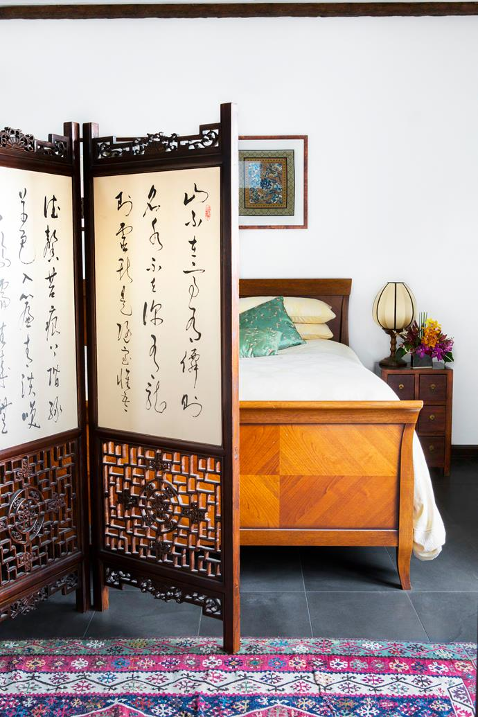 The custom-made screen in the main bedroom features panels of calligraphy by Wei's brother.   Vintage Italian **bed** bought in Canada.