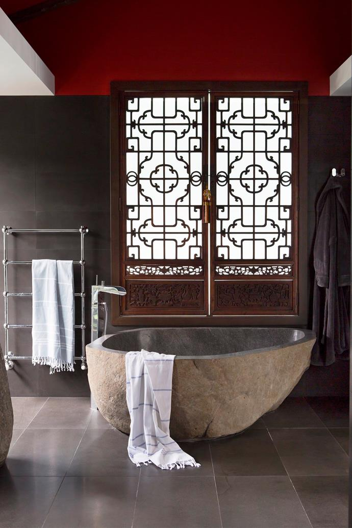 """The bath in the home's private retreat was carved from a single basalt boulder. """"The choice of textures was as important as the colours. I like organic forms, especially stone and wood,"""" says Karin.  Love Me **tapware** from [Paco Jaanson](http://www.pacojaanson.com.au/?utm_campaign=supplier/