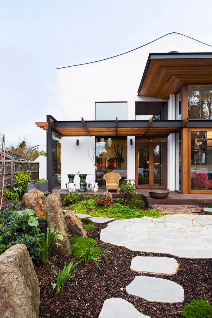 At the home's rear garden, the north-facing deck and living areas are shaded by wide cedar-lined eaves.