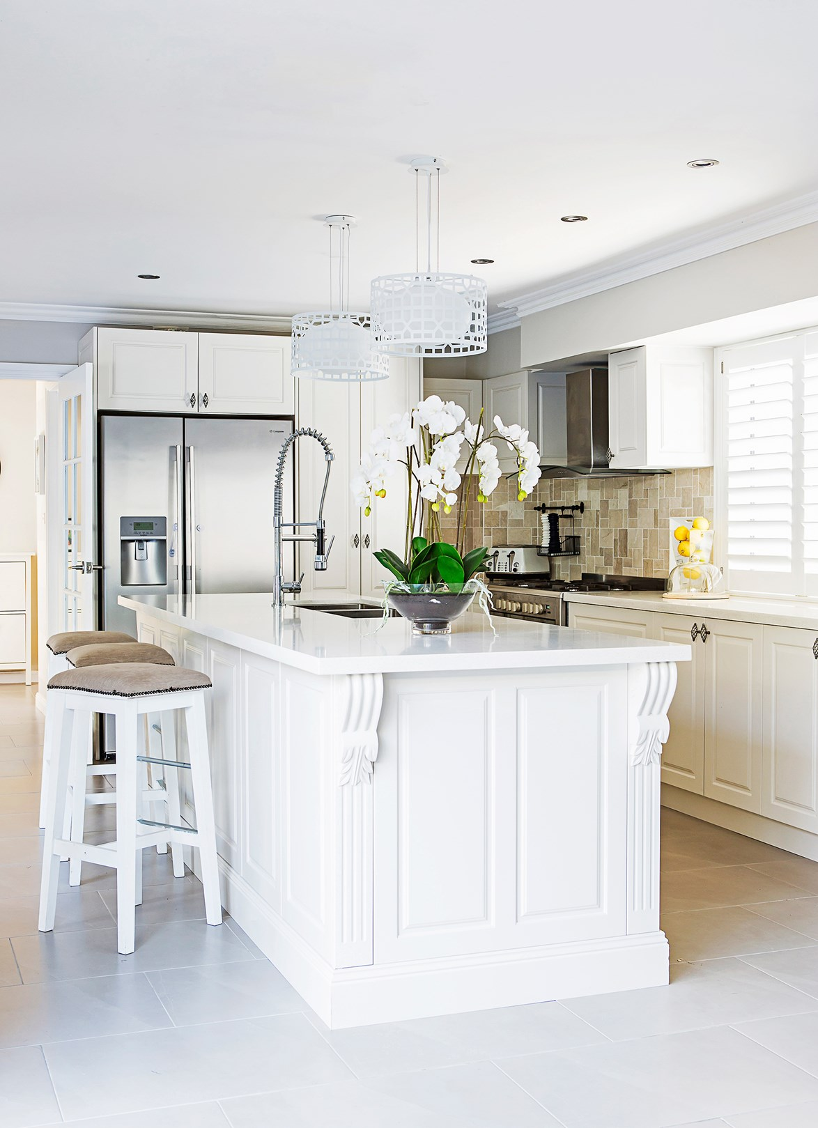 "Humble, but grand, is one way to summarise the French provincial look. This kitchen in a [stylishly renovated home](https://www.homestolove.com.au/cecilia-and-adrians-stylish-renovation-on-a-budget-2072 |target=""_blank""), features ornate cabinetry and sleek finishes but has, at the same time, been pared back with stools upholstered in earthy linen and a stone-tiled splashback. *Photo: Maree Homer*"