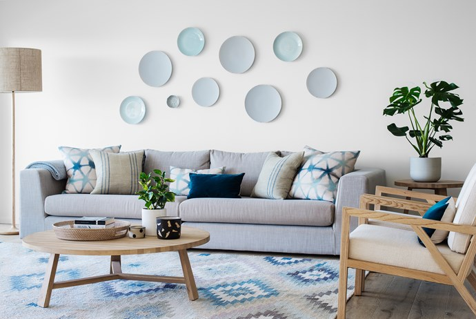 """Pattern plays a key role in the living room, where a potted *Monstera deliciosa* and a bubble-like display of wall-mounted assorted plates explore pattern to add interest to the space.   Old Yarn **kilim** from [Koskela](http://www.koskela.com.au/?utm_campaign=supplier/