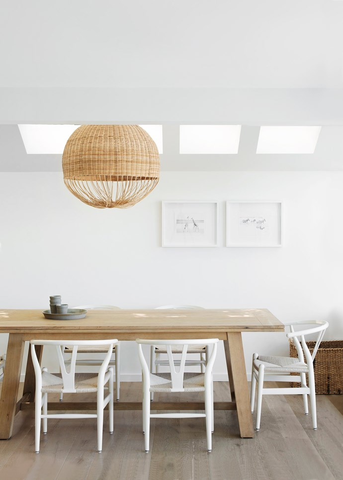 """Furnishings in solid oak and ash, including the dining table and chairs, as well as the flooring, have a sun-soaked patina. Simple pencil sketches from Africa hang on the dining room wall. """"The woven light fitting over the table is like a tumbleweed. We wanted something very tactile,"""" says Andrew.  Moloko pendant **light** from [MRD Home](http://www.mrdhome.com.au/?utm_campaign=supplier/