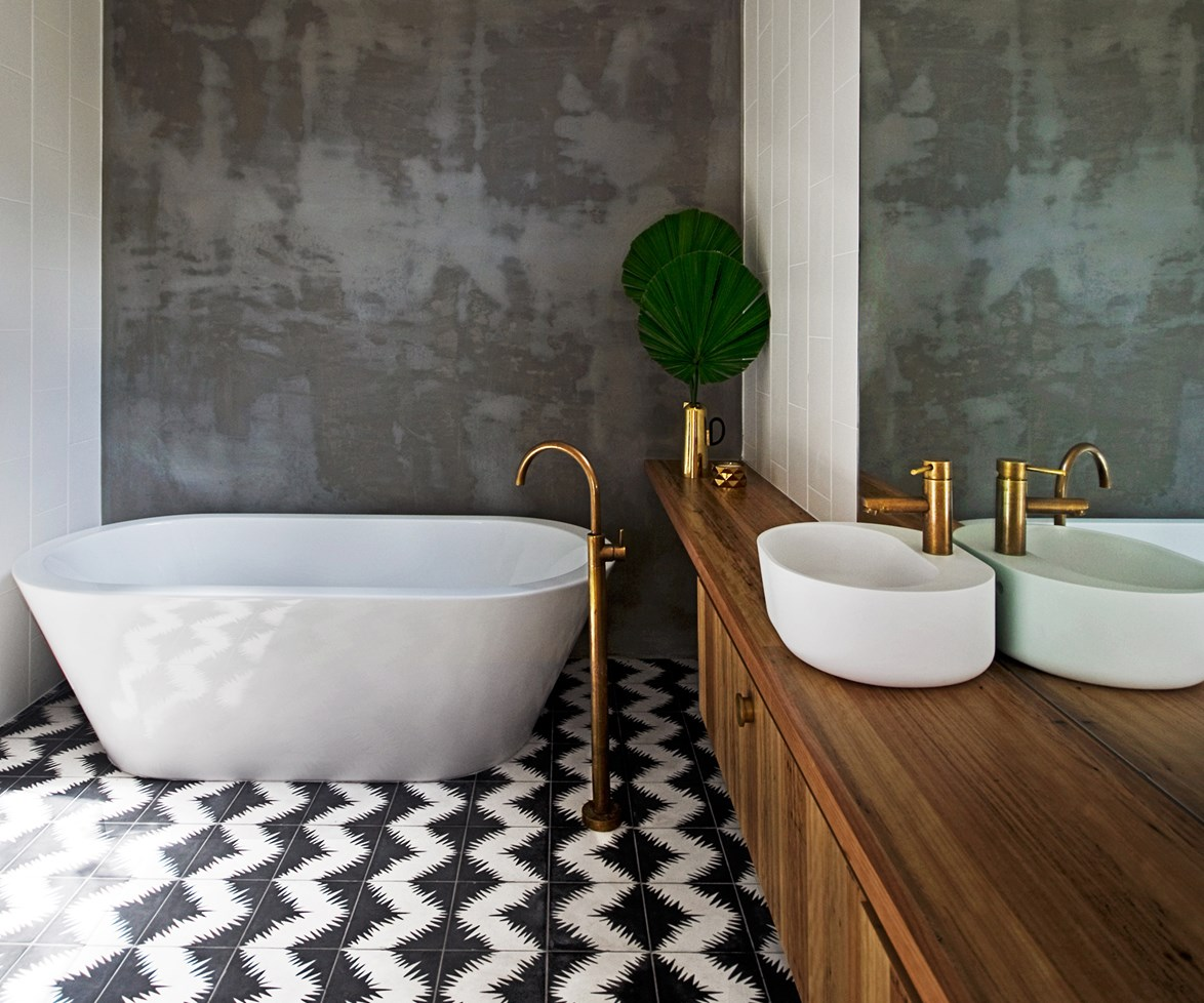 Timber, brass and concrete, contrast beautifully with the patterned monochrome tiles in this [industrial-style oasis](http://www.homestolove.com.au/bathroom-profile-brassed-beauty-2130) designed by [Auhaus Architecture & Interiors](http://auhaus-arch.com/). Photo: Trevor Mein