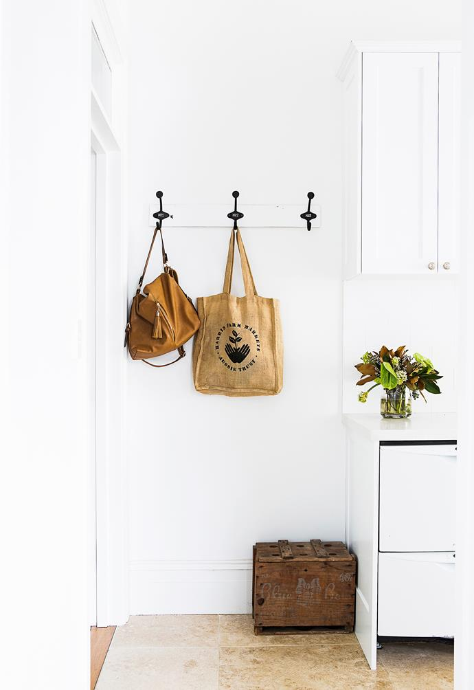 A charming row of coathooks by the kitchen is perfect for hanging shopping totes.