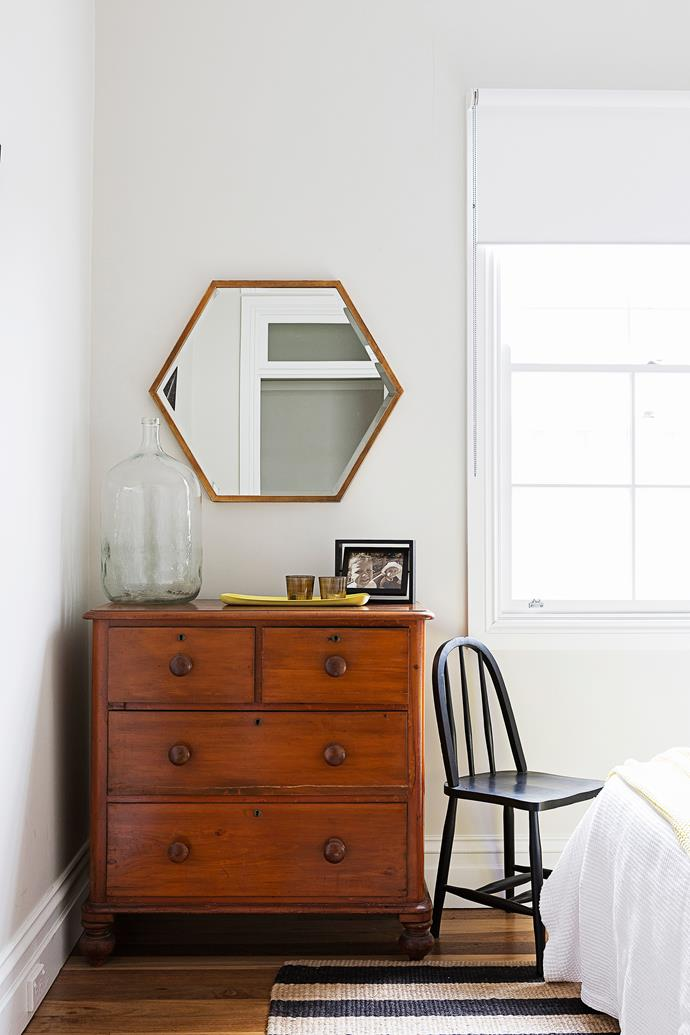 """A black-painted chair and polygon mirror in bronze from [Project 82](http://www.project82.com.au/?utm_campaign=supplier/