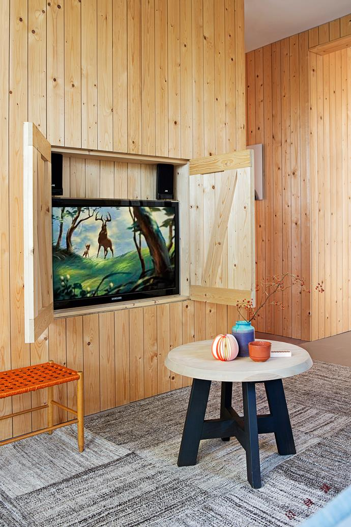 The TV can be hidden away when not in use, contributing to the home's uncluttered aesthetic.