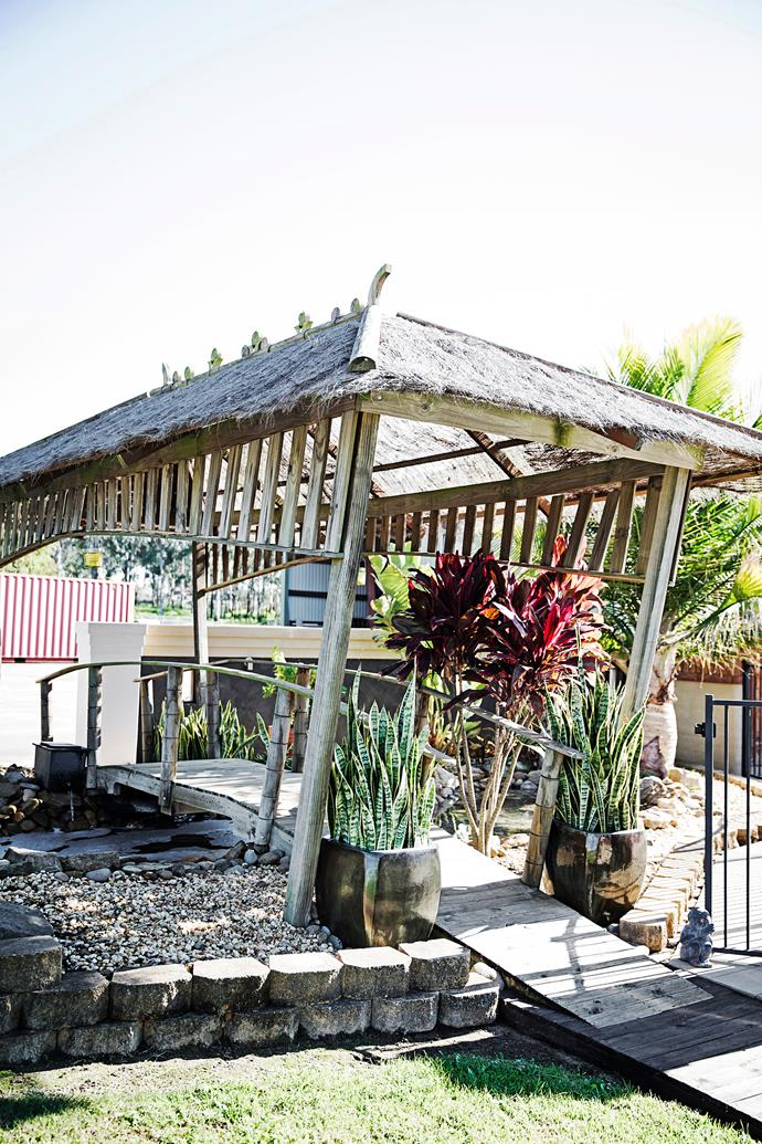 The homemade hut, bridge and pond add another tropical holiday element to the garden.