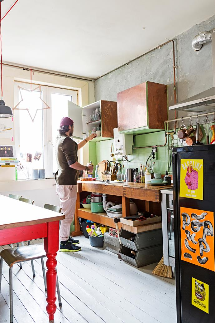 An old carpenter's workbench has found a new lease of life in the kitchen. Menne glued metallic copper panels onto the cupboards, while the wall was finished in concrete paint.