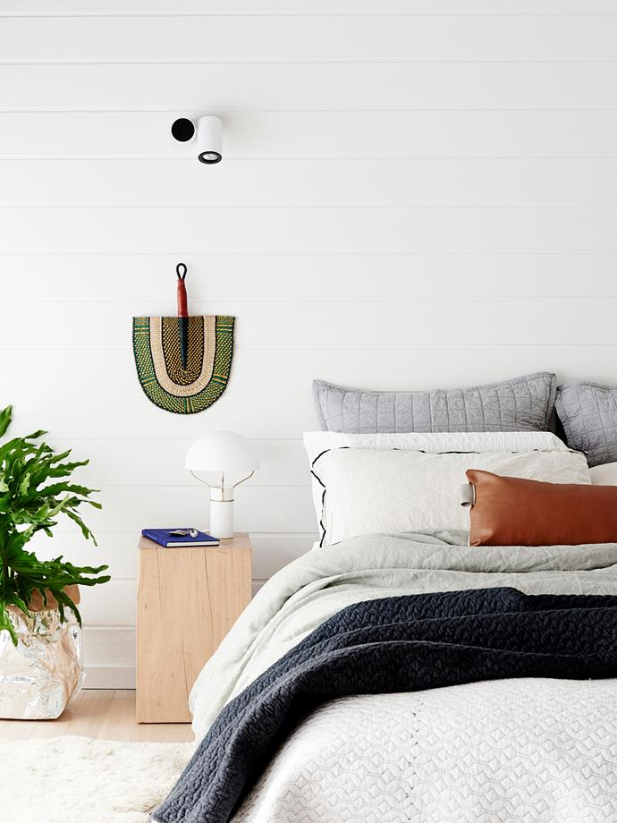 "The master bedroom is a lesson in textures. Nina snapped up the handwoven African fan hanging on the wall at a market near Byron Bay. A friend made the timber bedside table. The oversized metallic bag in silver is from [Uashmama](http://www.uashmama.com.au/?utm_campaign=supplier/|target=""_blank"")."